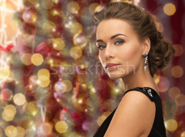 beautiful woman wearing earrings over lights Stock photo © dolgachov