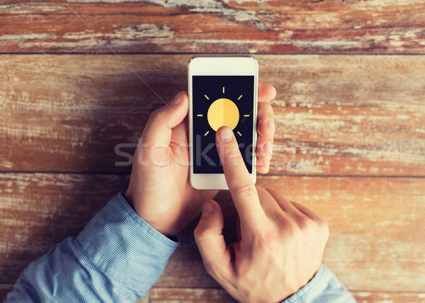 close up of hands with sun icon on smartphone Stock photo © dolgachov