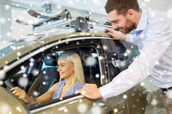 Stock photo: happy couple buying car in auto show or salon