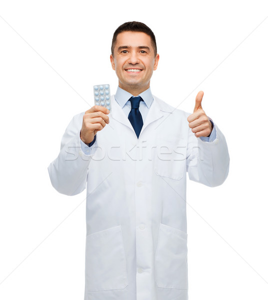 smiling male doctor in white coat with tablets Stock photo © dolgachov