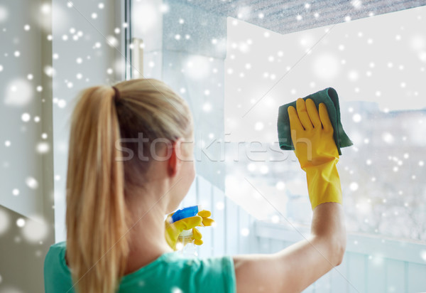 happy woman in gloves cleaning window with rag Stock photo © dolgachov