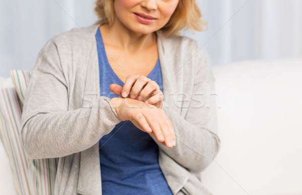 close up of woman suffering from hand inch at home Stock photo © dolgachov
