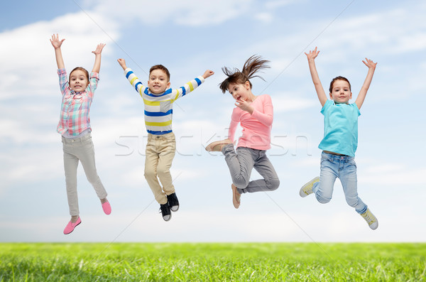 happy children jumping in air over sky and grass Stock photo © dolgachov