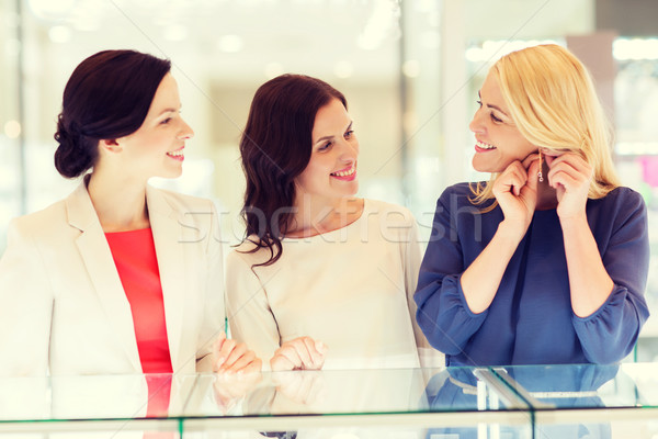 happy women choosing earrings at jewelry store Stock photo © dolgachov