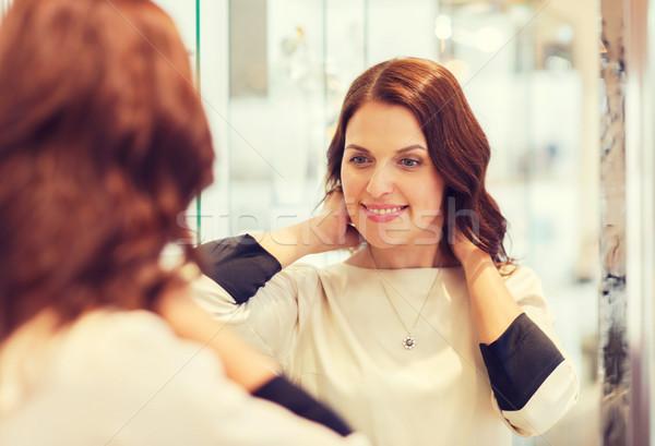 happy woman choosing pendant at jewelry store Stock photo © dolgachov