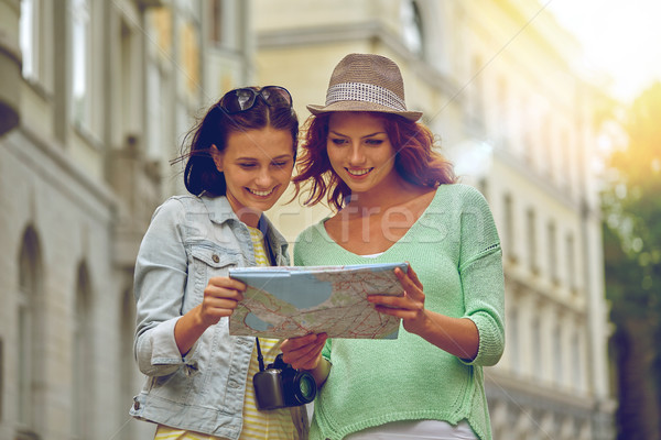 Glimlachend tienermeisjes kaart camera buitenshuis toerisme Stockfoto © dolgachov