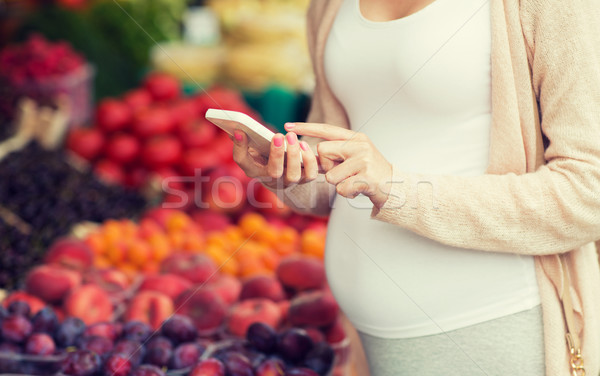 pregnant woman with smartphone at street market Stock photo © dolgachov