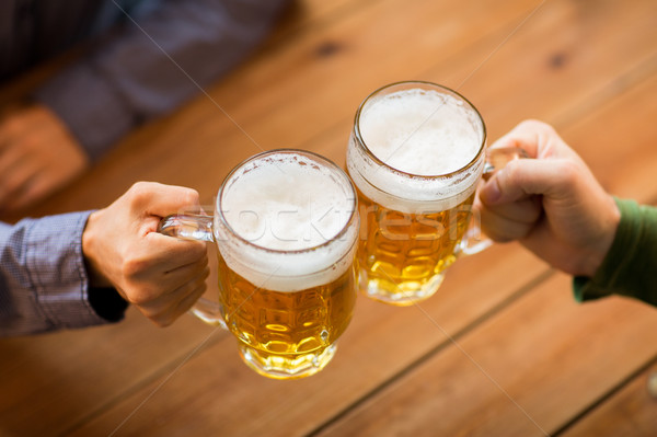 close up of hands with beer mugs at bar or pub Stock photo © dolgachov