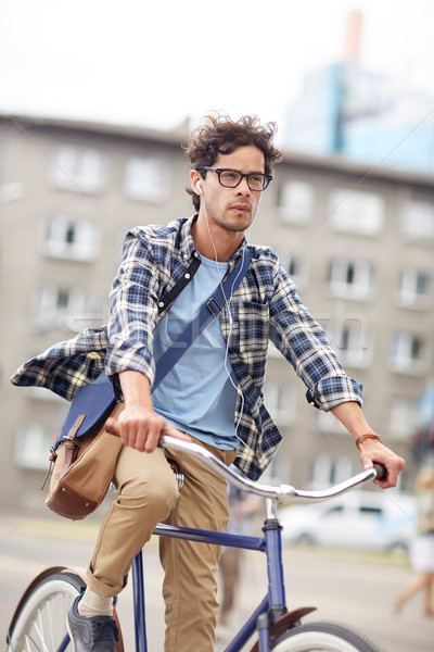 young hipster man with bag riding fixed gear bike Stock photo © dolgachov