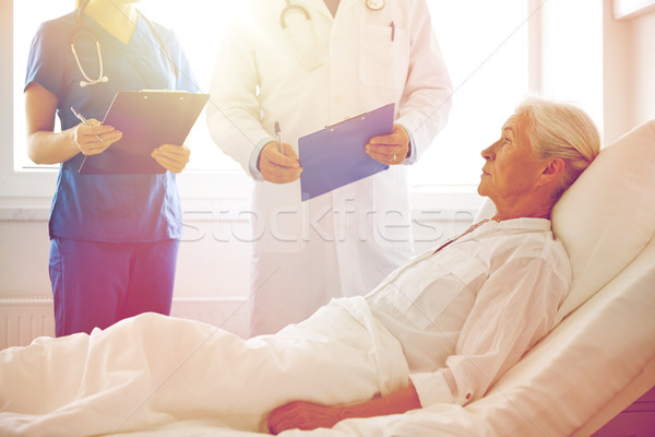 doctor and nurse visiting senior woman at hospital Stock photo © dolgachov