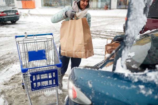 woman loading food from shopping cart to car trunk Stock photo © dolgachov