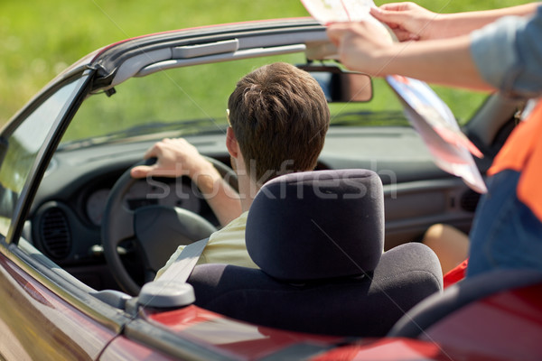 happy friends with map driving in convertible car Stock photo © dolgachov