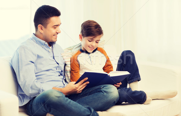 happy father and son reading book at home Stock photo © dolgachov
