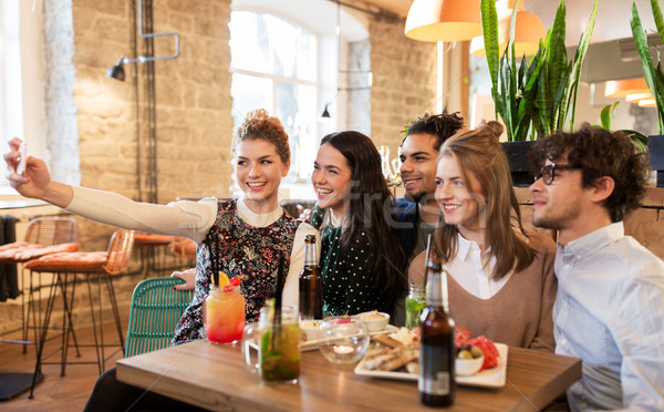 Stock photo: friends taking selfie by smartphone at bar or cafe