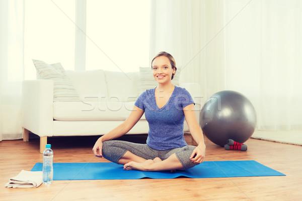 woman making yoga in lotus pose on mat Stock photo © dolgachov