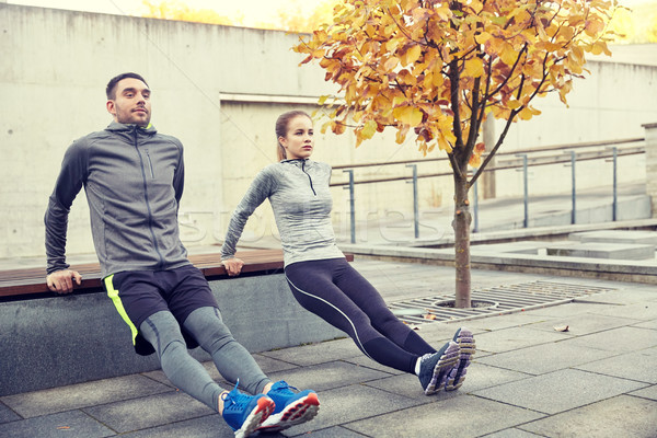 couple doing triceps dip on city street bench Stock photo © dolgachov