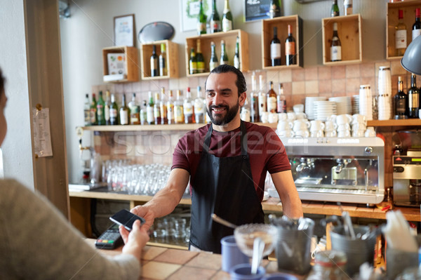 barman and woman with card reader and smartphone Stock photo © dolgachov