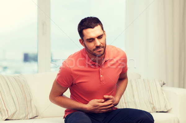 unhappy man suffering from stomach ache at home Stock photo © dolgachov