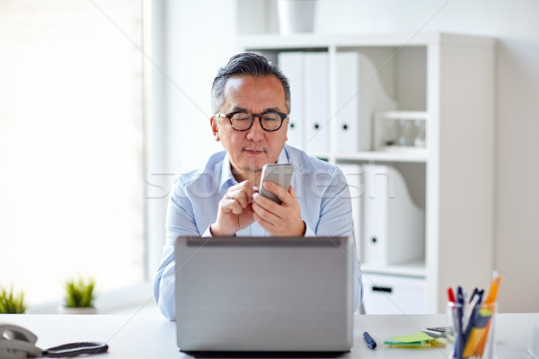 businessman with laptop texting on smartphone Stock photo © dolgachov