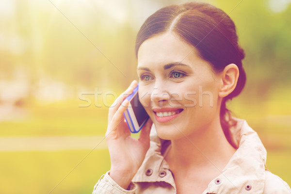 smiling woman calling on smartphone in park Stock photo © dolgachov