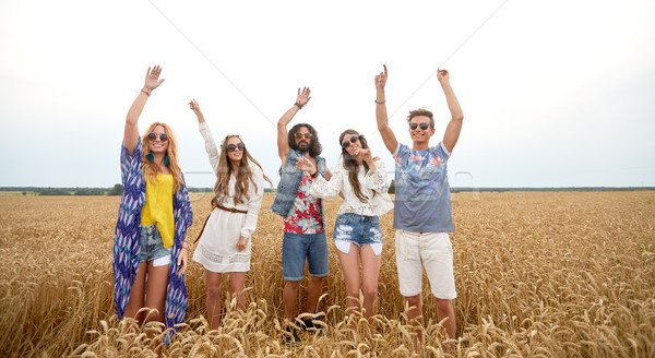 happy young hippie friends dancing on cereal field Stock photo © dolgachov