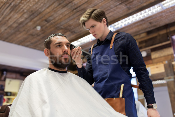 man and barber with trimmer cutting hair at salon Stock photo © dolgachov