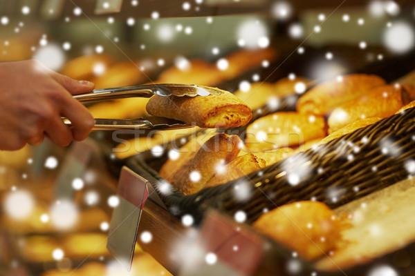 Mano tenazas toma bollo panadería comestibles Foto stock © dolgachov