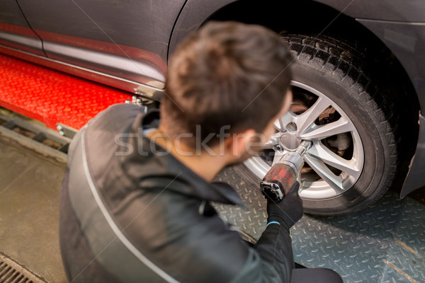 auto mechanic with screwdriver changing car tire Stock photo © dolgachov