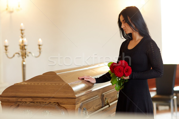 sad woman with red rose and coffin at funeral Stock photo © dolgachov
