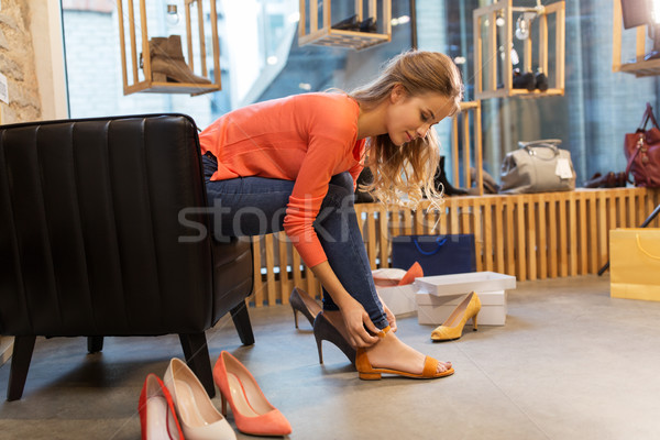 young woman trying sandals at shoe store Stock photo © dolgachov