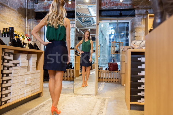 young woman in high-heeled shoes at store mirror Stock photo © dolgachov