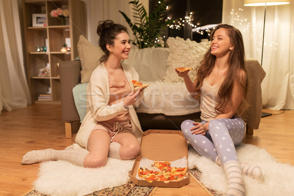 happy female friends with pizza at home Stock photo © dolgachov