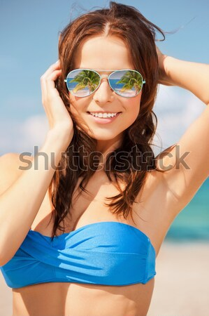 happy woman in sunglasses on the beach Stock photo © dolgachov