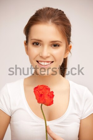 girl smelling flowers and holding postcard Stock photo © dolgachov