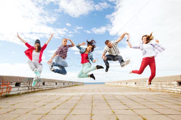 group of teenagers jumping Stock photo © dolgachov