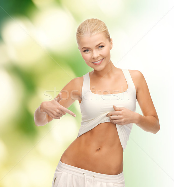 beautiful sporty woman pointing at her abs Stock photo © dolgachov