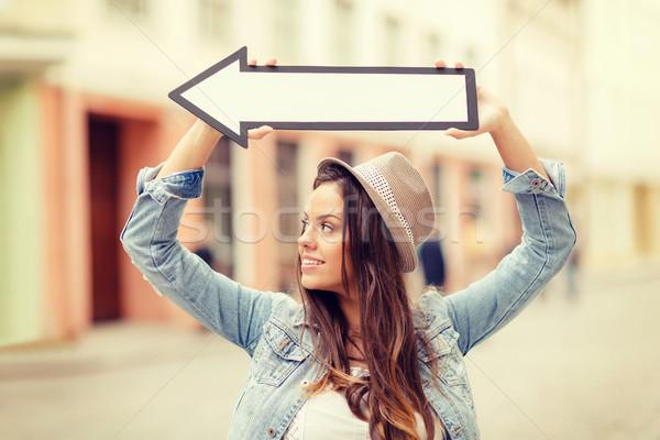 Meisje tonen richting pijl stad vakantie Stockfoto © dolgachov