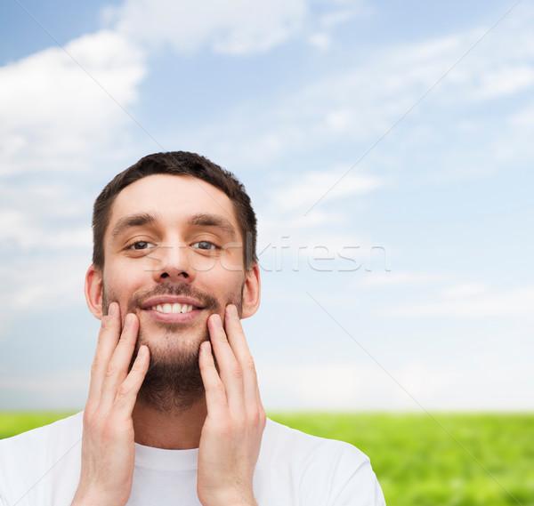 Belo sorridente homem tocante cara saúde Foto stock © dolgachov