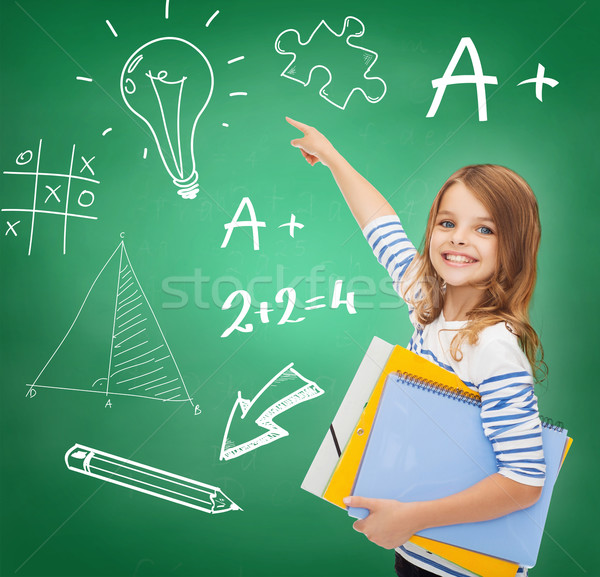 cute girl with folders pointing to green board Stock photo © dolgachov