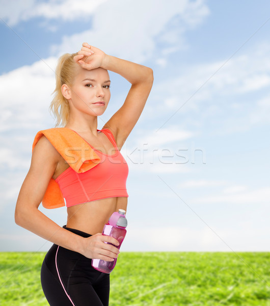 tired sporty woman with towel and water bottle Stock photo © dolgachov