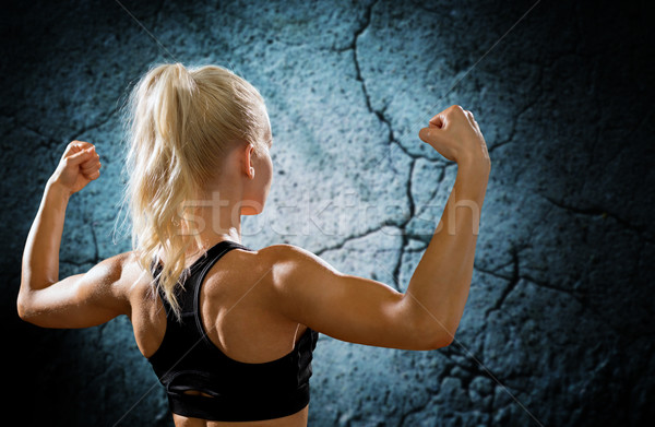sporty woman flexing and showing biceps from back Stock photo © dolgachov
