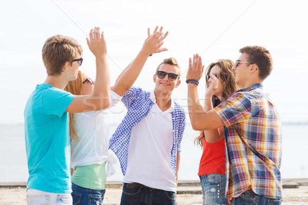 Groupe souriant amis high five extérieur Photo stock © dolgachov