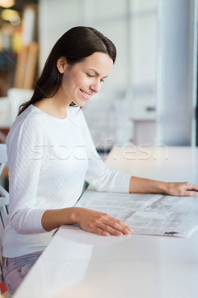 Stock photo: smiling young woman reading newspaper at cafe