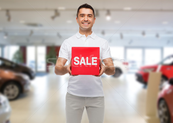 happy man with sale sigh over auto show background Stock photo © dolgachov