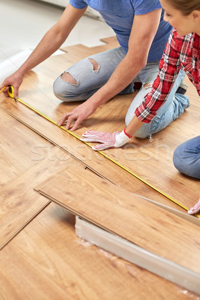 happy couple with ruler measuring parquet board Stock photo © dolgachov