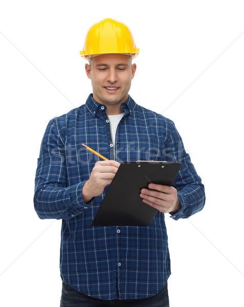 Sonriendo masculina constructor casco portapapeles reparación Foto stock © dolgachov