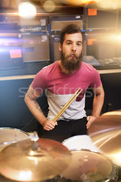 male musician playing cymbals at music store Stock photo © dolgachov