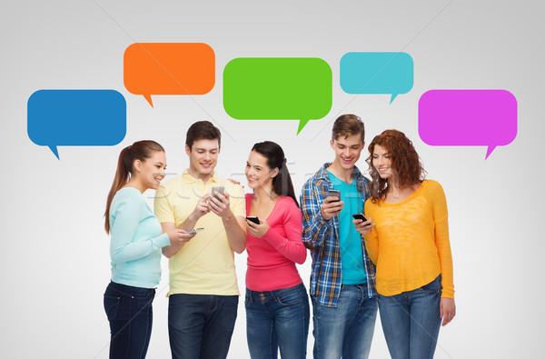 Groupe souriant adolescents smartphones amitié technologie Photo stock © dolgachov