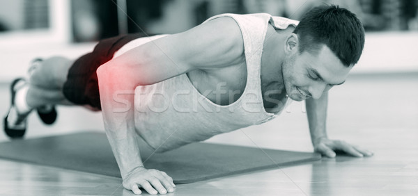 smiling man doing push-ups in gym Stock photo © dolgachov