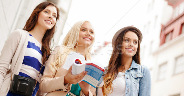 three beautiful girls with tourist book in city Stock photo © dolgachov